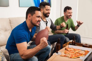 49825633 - profile view of a group of male friends cheering for their football team while watching the game at home