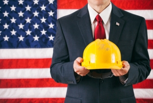 55385214 - politician: man holding up yellow hard hat